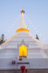 A white color of pagoda decorated by lighting at night time under clear sky located at north of Thailand