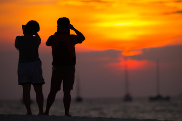 Happy romantic couple taking photo sunset on beach