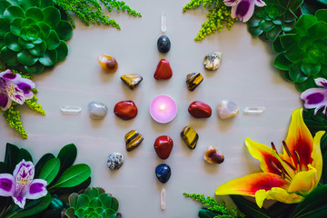 Crystal Grid with Candle Center on Grey Table with Summer Botanicals