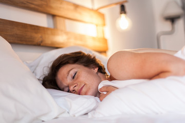 A beautiful woman wakes up in her bed