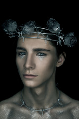Portrete of fashion young beautiful man in the image of a martyr with rose and thorns wreath. man on black background. Silver dark tone.