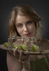 Beautiful woman with glasses of tequila and lime slices.