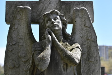 Sculpture of a praying angel on an old tomb of the cemetery of Montreal-Canada
