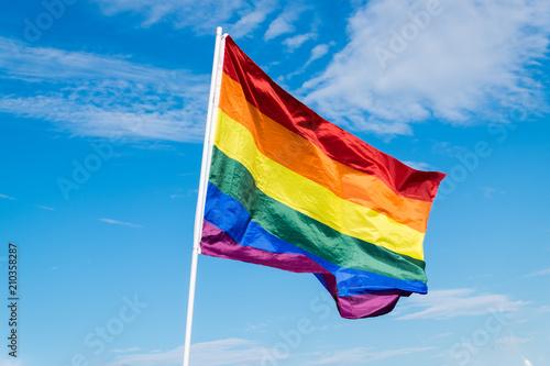 pride flag on a blue cloudy sky