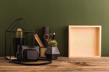 Close up on a vintage stylish desk with photo frame, books and a camera. Retro home decor.