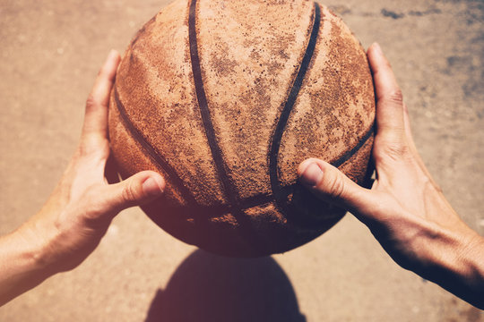 Old orange basketball in hand to play the sport.