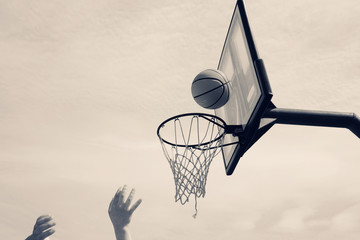 Vintage style monochrome sports image of hand shooting basketball at hoop off backboard.
