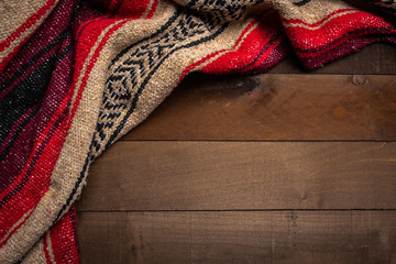A mexican serape blanket on a wooden plank background