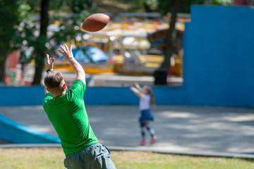 American Football Player Catching a touchdown Pass in park.