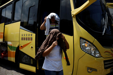 Deportees get off a bus at an immigration facility after a flight carrying illegal immigrants from the U.S. arrived in San Salvador