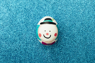 Detail of painted Easter eggs with form of clown on a shiny blue background