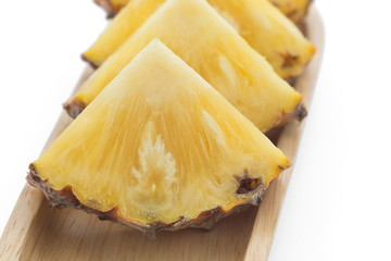 slice of pineapple on wooden plate.