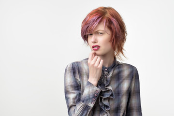 Portrait of unusual informal pretty woman with colorful hairstyle has a disgust expression on face.