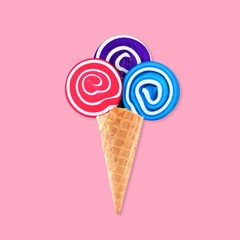 Ice cream waffle cone with lollipops against a pastel pink background