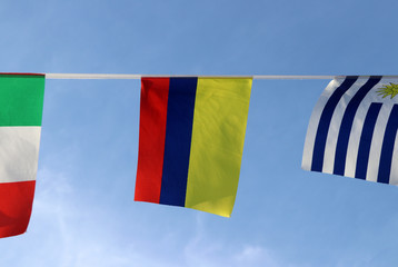 Mini fabric rail flag of Colombia in Tricolor Nacional yellow, blue and red color hanging on the rope cloth between the flag of other countries, on blue sky background.