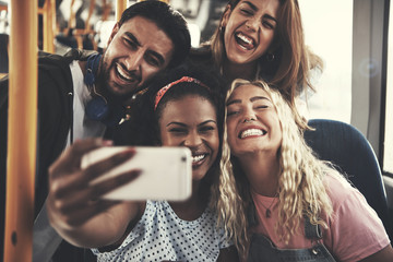 Laughing group of friends taking selfies together on a bus