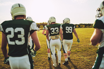 American football team walking together on a field during practi