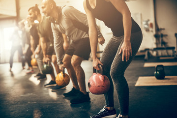 Fit people lifting dumbbells together during a workout session