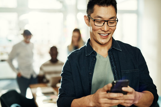 Smiling young Asian designer reading text messages in an office