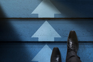 Challenge, Strategy and Leadership Concept. Businessman with Formal Shoes Steps Up and Followed Arrows and Lights on Stair. Top View