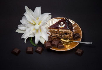 cut piece of chocolate cake on a yellow pearl plate with pieces of chocolate tiles on a black background and a lily flower