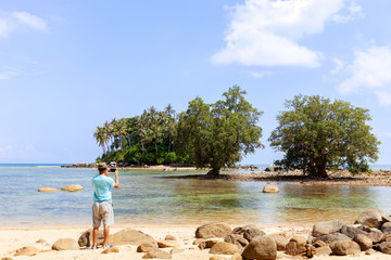 Travel man standing take a photo with smartphone ,beautiful small island in summer season at phuket thailand.