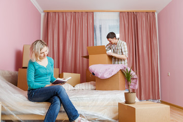 Photo of man and woman with book sitting on bed among cardboard boxes