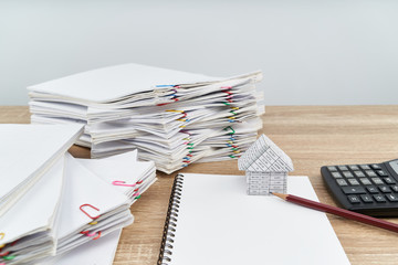 House and pencil on notebook with calculator white background