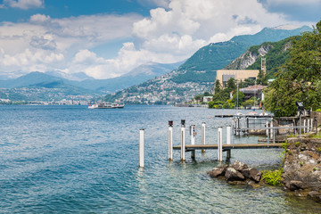 Lake Lugano. View of Campione d'Italia, famous for its casino (visible on the right), with a tourist boat arriving. In the background the city of Lugano and the Swiss Alps