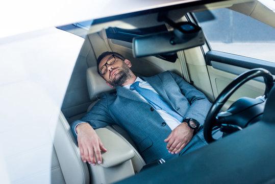 tired businessman in eyeglasses sleeping in car
