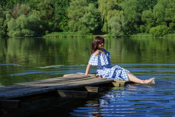 Young woman resting on a wooden bridge and wets feet in the river.