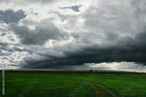grass field from above. Dark Storm Clouds Above The Green Grass Field From O