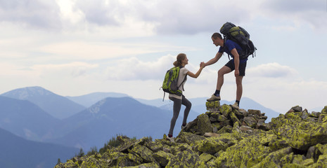 Photo sur cadre textile Alpinisme Young tourists with backpacks, athletic boy helps slim girl to clime rocky mountain top against bright summer sky and mountain range background. Tourism, traveling and healthy lifestyle concept.