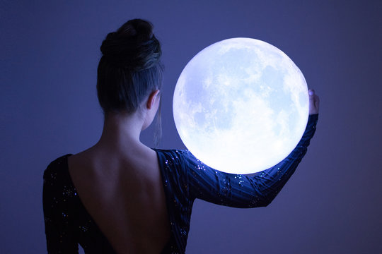 Elegant woman holding a big sphere glowing moon. Unrecognizable person, rear view