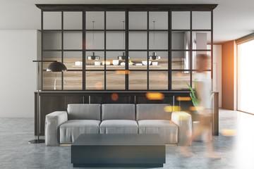 White and black living room, gray sofa, woman