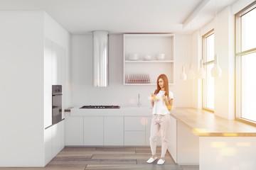 Woman in a white minimalist kitchen interior