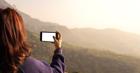 Women who are taking nature pictures with mobile phones to record memories during travel in various places.
