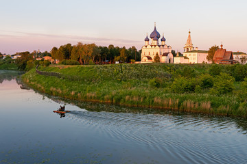 Suzdal town landscape. Suzdal is a gem of the Golden Ring of Russia route, famous tourist destination. Tourists took a Kamenka river paddleboat tour around Suzdal Kremlin.