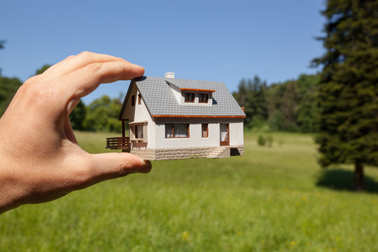 Dream to have a house. Hand holding a model house in green field