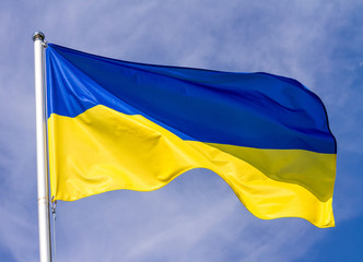 Flag of Ukraine waving in the wind on flagpole against the sky with clouds on sunny day, close-up
