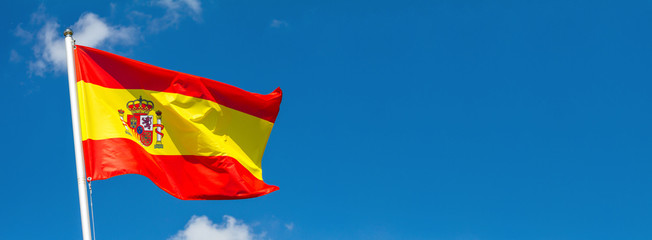 Flag of Spain waving in the wind on flagpole against the sky with clouds on sunny day, banner, close-up