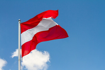 Flag of Austria waving in the wind on flagpole against the sky with clouds on sunny day, close-up