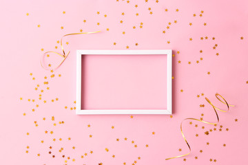 sparkles confetti and frame for inserting text on a colored background top view. Minimalism, design, insta, holiday. flatlay