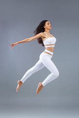 Attractive excited fitness girl, ballerina dancer in sportwear jumping of joy isolated over gray background.