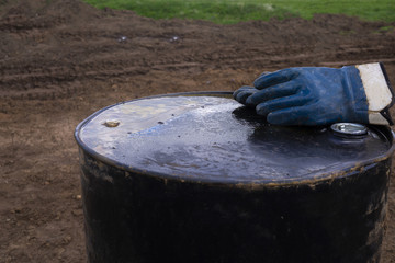 Dirty work gloves on rusty barrel. Gloves sitting on top of a whiskey barrel inside of oil