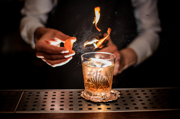 Poster Cocktail Barman making a fresh and tasty old fashioned cocktail with orange peel and smoke note