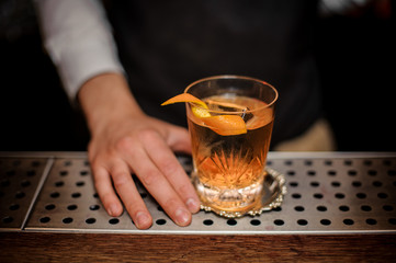 Bartender hand with a glass of fresh old fashioned summer cocktail with orange peel Wall mural