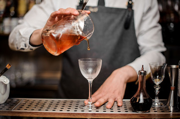 Bartender pouring fresh alcoholic drink into the cocktail glass