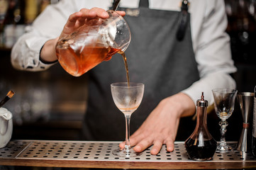 Barman pouring fresh alcoholic drink into the cocktail glass