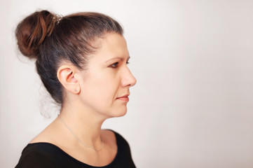 Portrait of a sad woman in a profile on a gray background. She looks to the side and gets sad because her hair is gray
